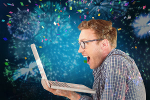 Geeky businessman using his laptop against colourful fireworks e